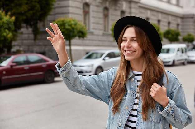 Jonge glimlachende jonge europese vrouw loopt buiten, zwaait met de hand als vriend aankondigt in de verte
