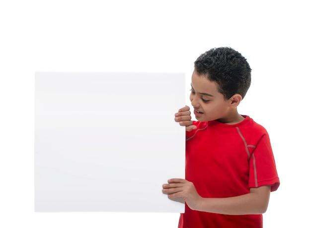 Jonge glimlachende jongen die witte raad met exemplaarruimte houdt
