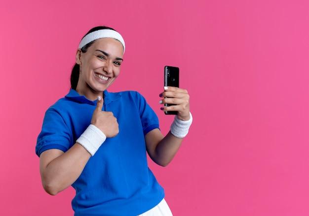 Jonge glimlachende kaukasische sportieve vrouw die hoofdband en polsbandjes draagt die omhoog telefoon houden die op roze achtergrond met exemplaarruimte wordt geïsoleerd