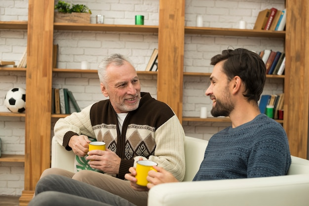 Jonge glimlachende kerel en de oude mens met koppen op sofa
