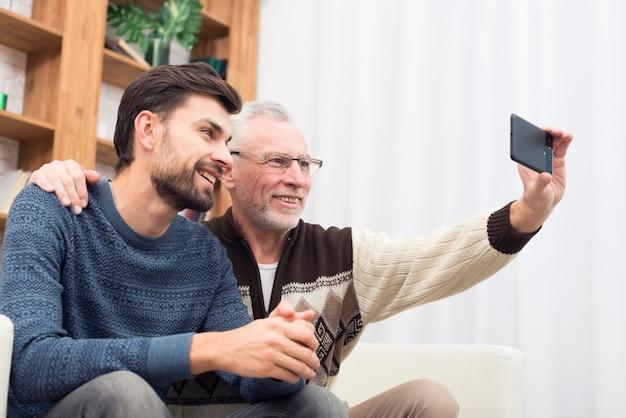 Jonge glimlachende kerel en de oude vrolijke mens die selfie op mobiele telefoon op sofa nemen