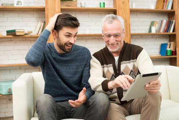 Jonge glimlachende kerel en de oude vrolijke mens die tablet op sofa gebruiken