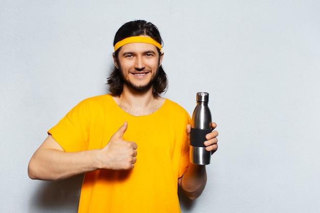 Jonge glimlachende kerel met oranje t-stuk die een aluminiumfles houdt en ok teken op witte achtergrond doet