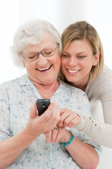 Jonge glimlachende kleindochter die en een mobiele telefoon toont aan haar grootmoeder