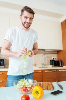 Jonge glimlachende man bereidt sald in de keuken en kijkt naar de voorkant