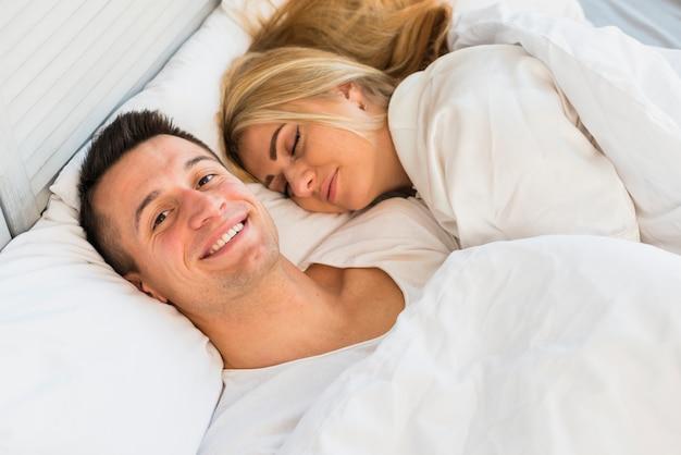 Jonge glimlachende man dichtbij slaapvrouw onder deken op bed
