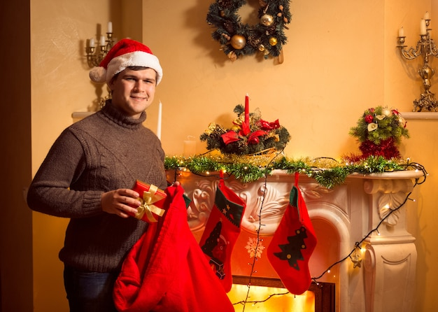 Jonge glimlachende man die cadeautjes in kerstsokken steekt die aan de open haard hangen