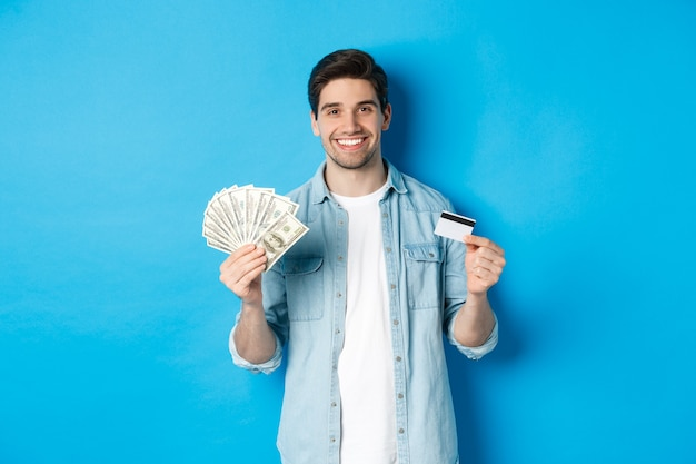Jonge glimlachende man die contante dollars en creditcard toont, staande over blauwe achtergrond