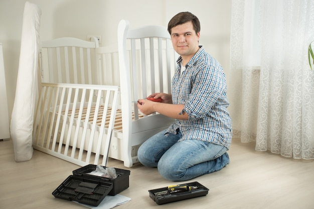 Jonge glimlachende man die meubels in de kinderkamer uit elkaar haalt