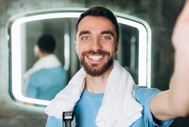 Jonge glimlachende man met handdoek die een gloednieuw scheerapparaat vasthoudt en vroeg in de ochtend een selfie maakt in de badkamer.