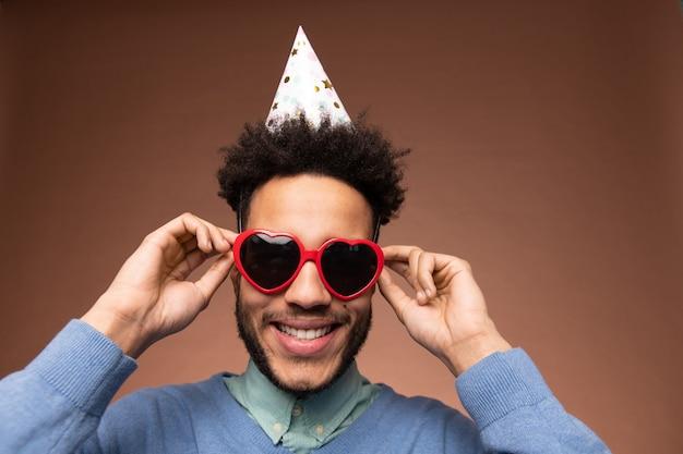 Jonge glimlachende man van gemengd ras in slimme vrijetijdskleding en verjaardagspet die een hartvormige zonnebril aanraakt terwijl hij voor de camera staat