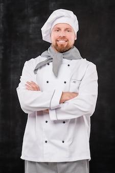Jonge glimlachende mannelijke chef-kok die wapens door borst kruist terwijl u tegen zwarte achtergrond kijkt