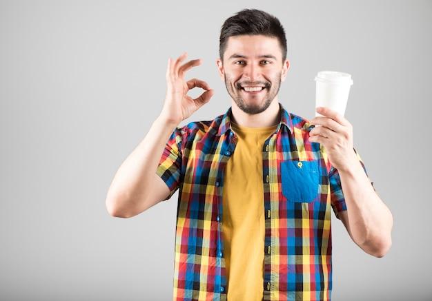 Jonge glimlachende mens met koffiekop die ok teken toont