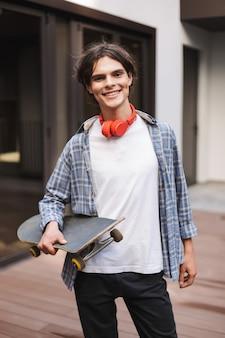 Jonge glimlachende mens met rode hoofdtelefoons die en skateboard staan terwijl vreugdevol