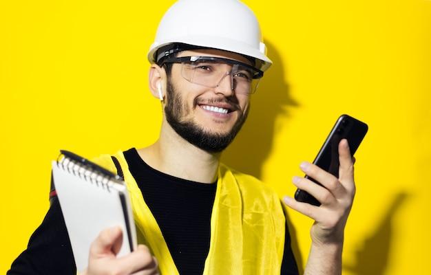 Jonge glimlachende mensenarchitect, bouwersingenieur, die witte bouwveiligheidshelm, glazen en jasje dragen. met behulp van smartphone en draadloze oortelefoons, geïsoleerd op gele muur.