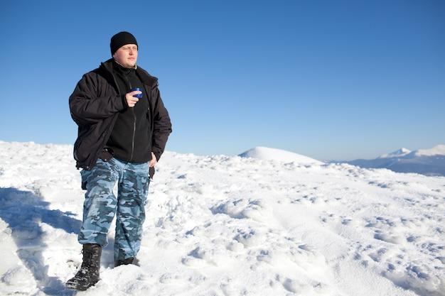Jonge glimlachende mensenfotograaf in de winterkleding het drinken van thee van thermosflessen
