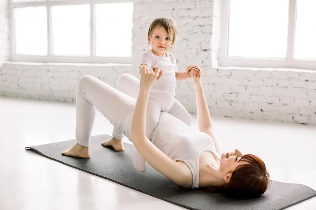 Jonge glimlachende moeder die yogaoefening doet bij gymnastiek, witte sportkleding draagt, samen met grappig dochtertje, genietend van activiteiten met baby, pret en sportpraktijk