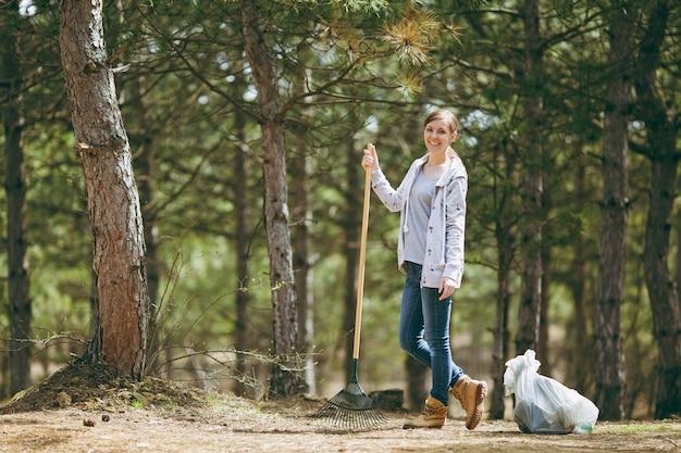 Jonge glimlachende mooie vrouw die hark schoonmaakt en gebruikt voor het ophalen van afval in de buurt van vuilniszakken in park of bos. probleem van milieuvervuiling