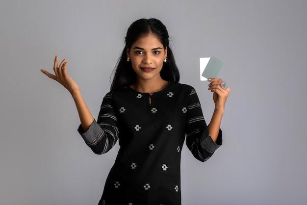 Jonge glimlachende mooie vrouw of meisje die in hand creditcard voorstellen die vertrouwen en vertrouwen voor het doen van betaling tonen.