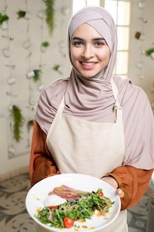 Jonge glimlachende moslimvrouw met bord met zelfgemaakte groentesalade met saus en gerookt vlees terwijl ze voor de camera staan