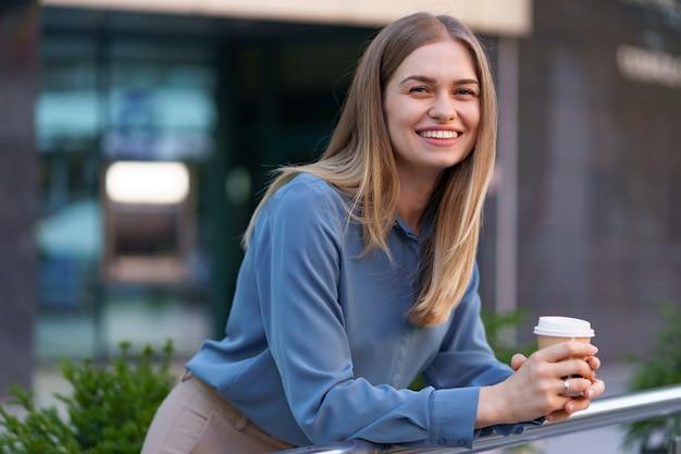 Jonge glimlachende professionele vrouw die een koffiepauze heeft tijdens haar volledige werkdag. ze houdt een papieren beker buiten bij het bedrijfsgebouw terwijl ze ontspant en geniet van haar drankje.