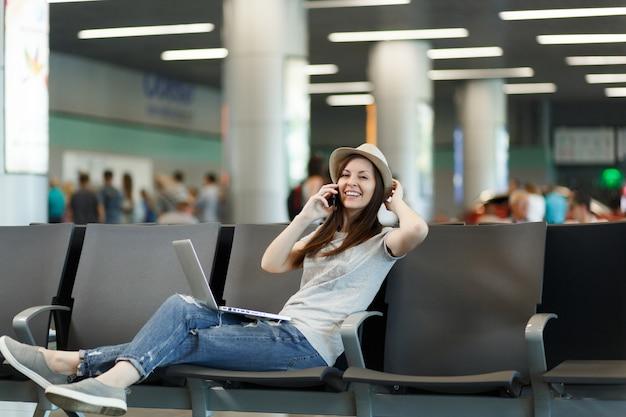 Jonge glimlachende reiziger toeristische vrouw die op laptop werkt, praat op mobiele telefoon, belt vriend op luchthaven