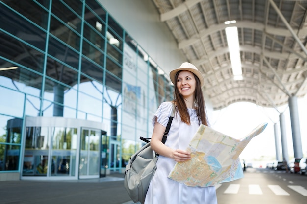 Jonge glimlachende reiziger toeristische vrouw in hoed, lichte kleding houdt papieren kaart op internationale luchthaven