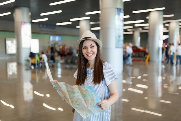 Jonge glimlachende reiziger toeristische vrouw in hoed met papieren kaart, route zoeken tijdens het wachten in de lobby hal op de internationale luchthaven