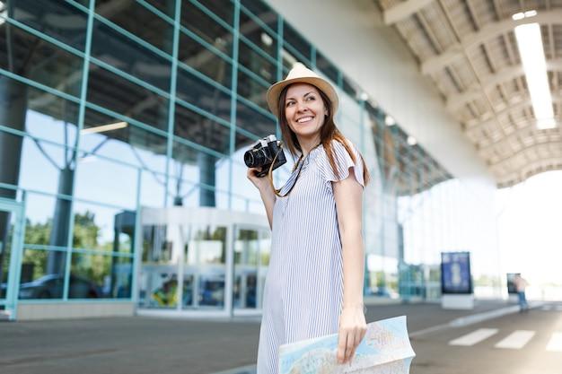 Jonge glimlachende reiziger toeristische vrouw in hoed met retro vintage fotocamera, papieren kaart op internationale luchthaven