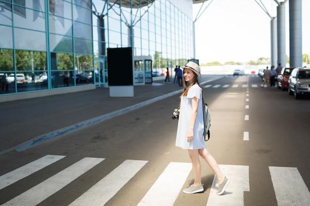 Jonge glimlachende reiziger toeristische vrouw in hoed met rugzak, retro vintage fotocamera op zebrapad op internationale luchthaven
