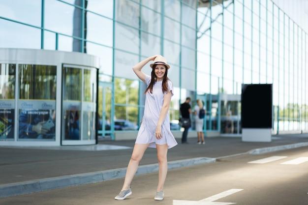 Jonge glimlachende reizigerstoerist in hoed en lichte kleding die op de internationale luchthaven staat