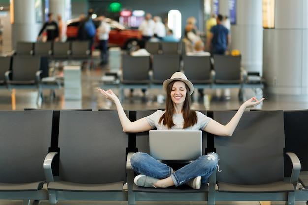 Jonge glimlachende reizigerstoerist met laptop die met gekruiste benen zit, mediteert, handen spreidt, wacht in de lobby op de luchthaven