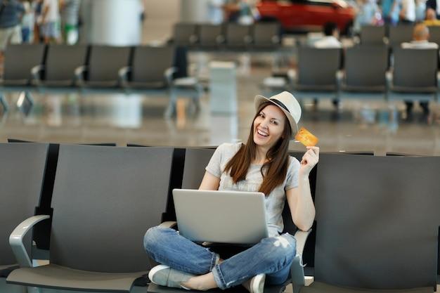 Jonge glimlachende reizigerstoeristenvrouw in hoed zit met gekruiste benen, werkend op laptop, houd creditcard in de lobby op de luchthaven