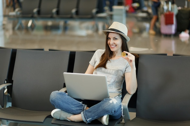 Jonge glimlachende reizigerstoeristenvrouw in hoed zit met gekruiste benen, werkend op laptop met bitcoin, wachtend in lobbyhal op luchthaven