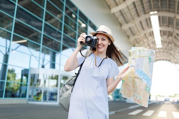 Jonge glimlachende reizigerstoeristenvrouw maakt foto's op retro vintage fotocamera, met papieren kaart op internationale luchthaven