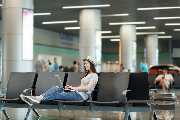 Jonge glimlachende reizigerstoeristenvrouw met hoed die aan laptop werkt terwijl ze wacht in de lobby op de internationale luchthaven