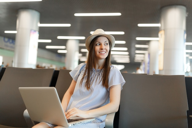 Jonge glimlachende reizigerstoeristenvrouw met hoed die op laptop werkt, opzij kijkend terwijl ze wacht in de lobbyhal op de internationale luchthaven