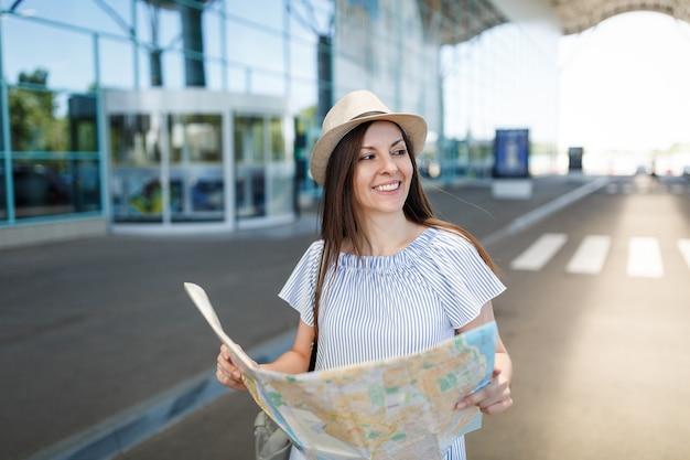 Jonge glimlachende reizigerstoeristenvrouw met hoed houdt papieren kaart vast en kijkt opzij naar de internationale luchthaven