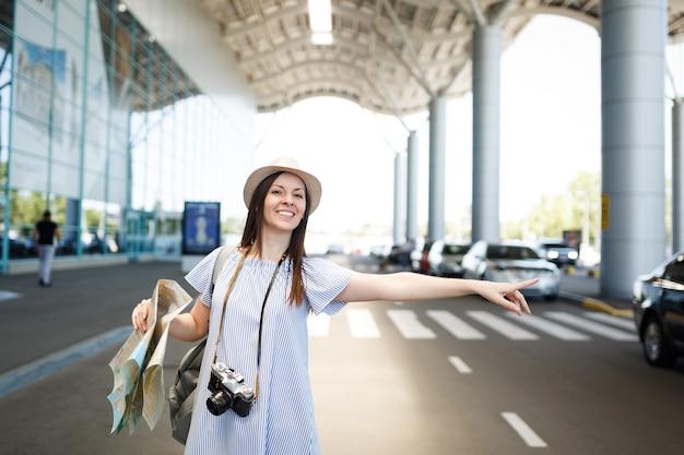Jonge glimlachende reizigerstoeristenvrouw met rugzak, retro vintage fotocamera houdt papieren kaart vast, vangt taxi op internationale luchthaven
