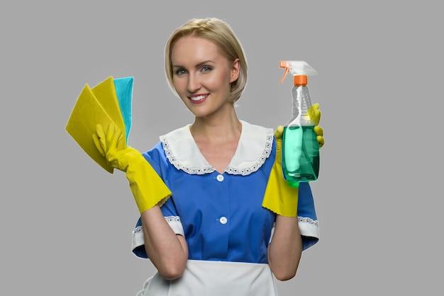 Jonge glimlachende schonere vrouw. jonge mooie vrouw meid in uniforme vodden en fles schoonmaak spray. schoonmaak concept.