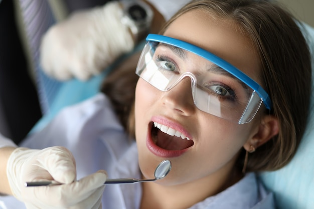 Jonge glimlachende schoonheidsvrouw in het portret van het dentinstbureau