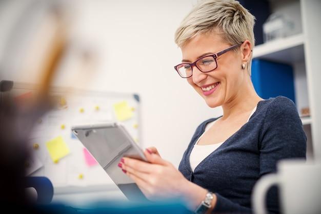 Jonge glimlachende secretaresse zit in haar kantoor en kijkt naar tablet.