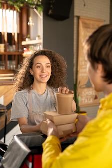 Jonge glimlachende serveerster die koerier bekijkt die voor haar staat terwijl hij hem helpt om bestellingen van klanten in een grote zak in restaurant te verpakken