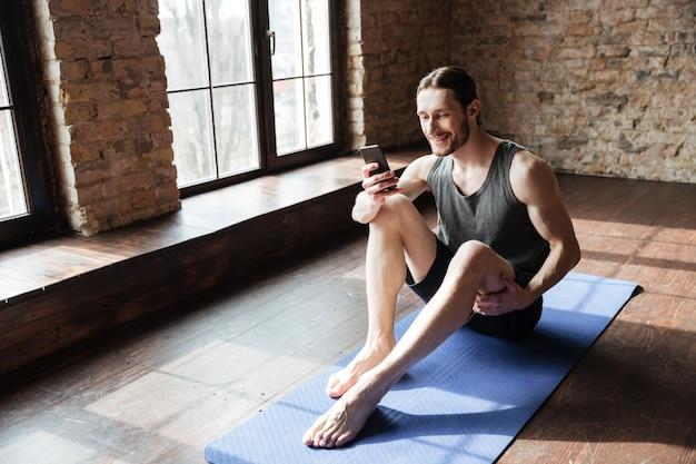 Jonge glimlachende sportman die mobiele telefoon met behulp van terwijl het zitten