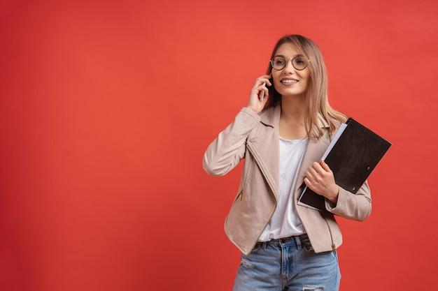 Jonge glimlachende student of stagiair in oogglazen die op de telefoon spreken terwijl status met een omslag