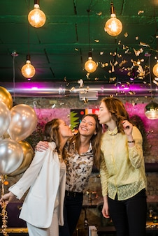 Jonge glimlachende vrienden die kus geven aan haar vriend in partij