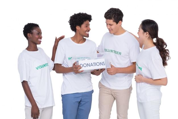 Jonge glimlachende vrijwilligers die schenkingen verzamelen