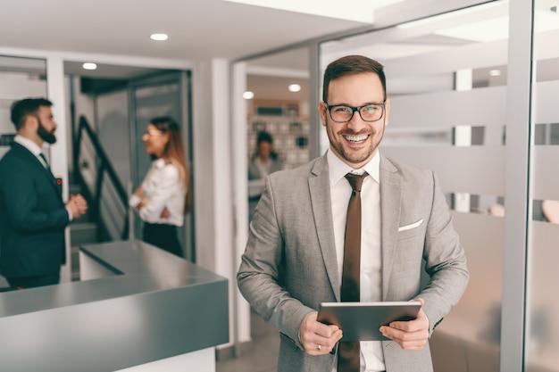 Jonge glimlachende vrolijke kaukasische zakenman in formele slijtage die zich in gang bevindt en tablet houdt.