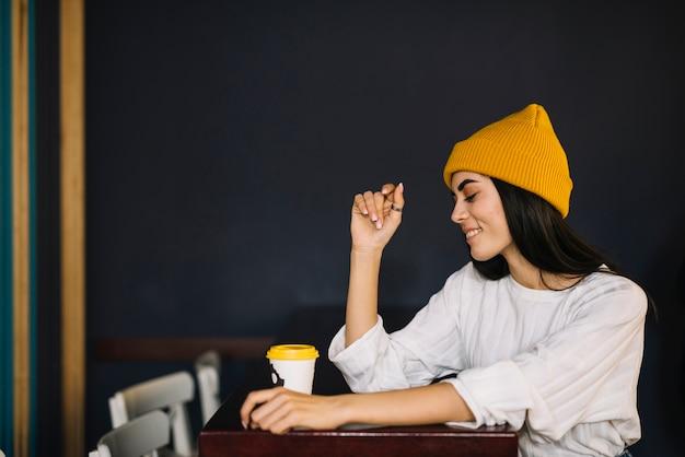 Jonge glimlachende vrouw dichtbij kop van drank bij lijst