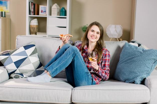 Jonge glimlachende vrouw die avond thuis doorbrengen, op de bank zitten, wijn drinken en pizza eten